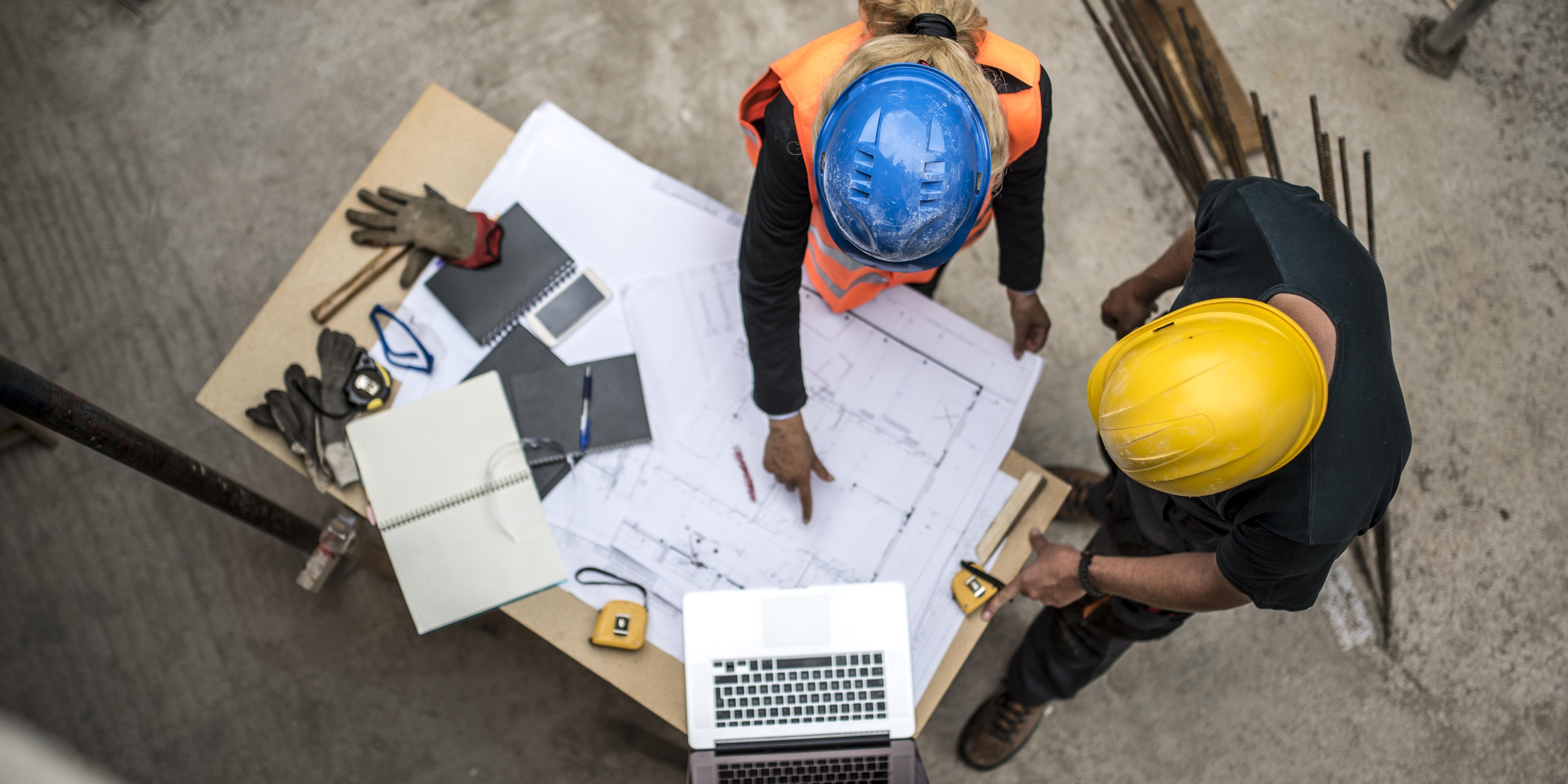 Two architects examining the blueprints on construction site
